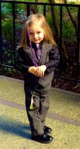 Picture of a little boy with a purple dreadlock, wearing a suit.