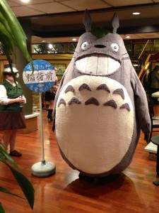 Person in a Totoro costume, with a road sign in Japanese