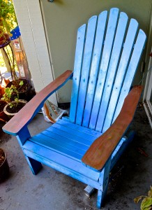 Picture of a blue Adirondack chair with copper arms.