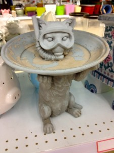 Image of a birdbath in the shape of a cat with a scuba mask.