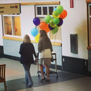 photo of two women in a hospital corridor with balloons