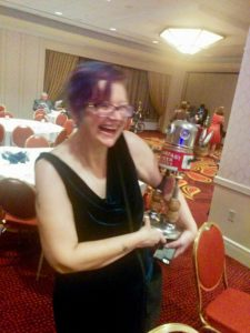 Picture of SFWA President Cat Rambo holding a small robot sculpture