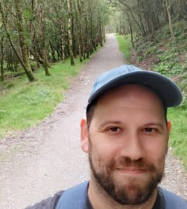 Selfie of Ziv Wities on a path through a forest.