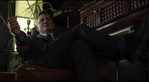 Character relaxing smugly in a chair as he observes investigation.