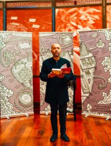 Henry Lien reading in front of large stylized map from Peasprout Chen.